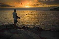 Pêcheur sur le rivage de l'océan au coucher du soleil Photographie stock libre de droits