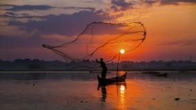 Pêcheur sur les poissons en bois de crochet de silhouette de bateau au lac pendant le matin Photographie stock