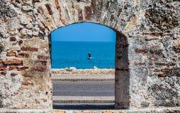 Pêcheur sur son bateau vu l'embrasure des murs de ville à Carthagène photo stock