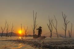Pêcheur sur un bateau en bois avec le fond de coucher du soleil Image stock