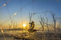 Pêcheur sur un bateau en bois avec le fond de coucher du soleil Photo stock