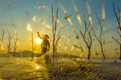 Pêcheur sur un bateau en bois avec le fond de coucher du soleil Photo libre de droits