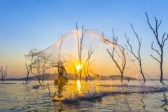 Pêcheur sur un bateau en bois avec le fond de coucher du soleil Photographie stock