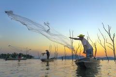 Pêcheur sur un bateau en bois avec le fond de coucher du soleil Images stock