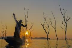 Pêcheur sur un bateau en bois avec le fond de coucher du soleil photographie stock libre de droits