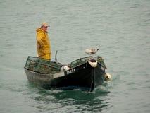 Pêcheur sur une silhouette de bateau Image stock