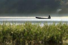 Pêcheur sur une silhouette de bateau Photos stock