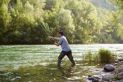 Pêcheur tenant la rivière proche et tenant la canne à pêche Photo stock