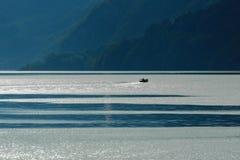Pêcheur voyageant sur un lac suisse Image libre de droits