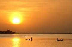 Pêcheurs africains dans des canoës au coucher du soleil images stock
