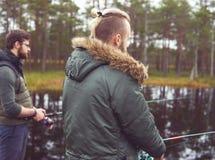 Pêcheurs avec un poisson contagieux de tige de rotation sur une rivière Photo stock