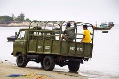 Pêcheurs conduisant la voiture sur la plage avec les bateaux de pêche colorés le 7 février 2012 en Mui Ne, Vietnam Photo libre de droits