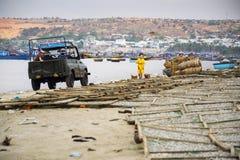 Pêcheurs conduisant la voiture sur la plage avec les bateaux de pêche colorés le 7 février 2012 en Mui Ne, Vietnam Photos libres de droits