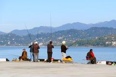 Pêcheurs dans le port sur le fond de la pêche de montagnes Images stock