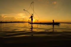 Pêcheurs et enfants pêchant en rivière qu'une couleur d'or silhouettent Image libre de droits