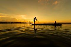 Pêcheurs et enfants pêchant en rivière qu'une couleur d'or silhouettent Photographie stock libre de droits