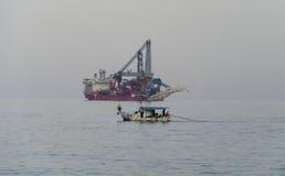 Pêcheurs jetant des filets de pêche contre le bateau moderne photographie stock libre de droits