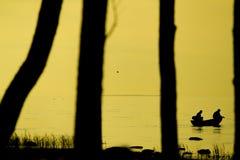 Pêcheurs pêchant sur la plage pendant au coucher du soleil Photographie stock