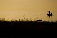 Pêcheurs pêchant sur la plage pendant au coucher du soleil Images stock