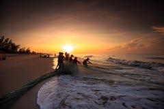 Pêcheurs qui traînent des filets au lever de soleil Images libres de droits