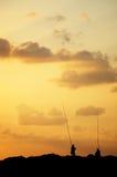 Pêcheurs silhouettés au coucher du soleil Photographie stock libre de droits