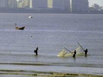 Pêcheurs soulevant le filet en mer Photographie stock