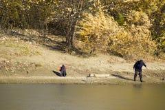 Pêcheurs sur la banque de la rivière en automne Pêche de l'amorce Photos libres de droits