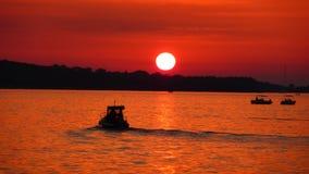 Pêcheurs sur la mer au coucher du soleil rouge Photos libres de droits