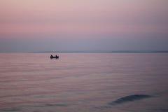 Pêcheurs sur un bateau en mer au lever de soleil Images libres de droits