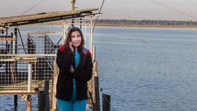 Pêcheuse au téléphone près de sa hutte de pêche Photographie stock