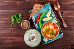Pêchez la soupe avec des saumons et des crevettes, aneth, des pommes de terre, citron, des poivrons et pain sur le fond en bois f Photo stock