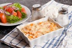 Pêchez le gratin avec de la crème, le fromage et le potiron Julienne française de plat Image libre de droits