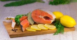 Pêchez les saumons, le citron et les verts placés sur la table. Images stock