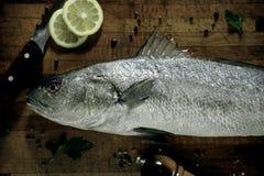 Pêchez sur la table et les mains en bois nettoyant des poissons Image stock