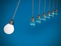 Pêndulo dos trabalhos de equipa do conceito dos bulbos no azul Fotografia de Stock