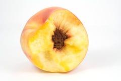 Pêssego suculento mordido no branco Fotos de Stock