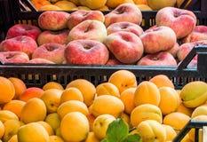Pêssegos da filhós e abricós grandes em umas caixas plásticas no mercado de fruto da rua fotografia de stock royalty free