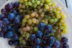 Pêssegos e uvas em uma placa na tabela Imagem de Stock