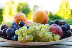 Pêssegos e uvas em uma placa na tabela Imagens de Stock Royalty Free