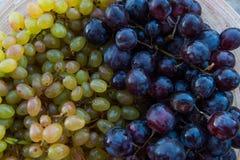 Pêssegos e uvas em uma placa na tabela Fotos de Stock
