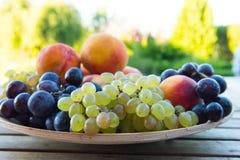 Pêssegos e uvas em uma placa na tabela Fotografia de Stock