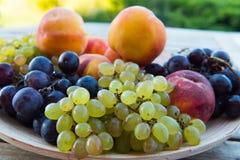 Pêssegos e uvas em uma placa na tabela Imagens de Stock
