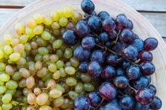 Pêssegos e uvas em uma placa na tabela Fotografia de Stock Royalty Free