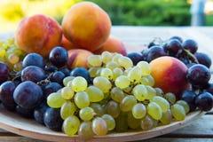 Pêssegos e uvas em uma placa na tabela Fotos de Stock Royalty Free