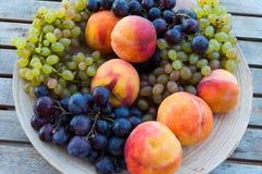 Pêssegos e uvas em uma placa na tabela Foto de Stock