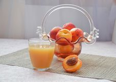 Pêssegos e vidro maduros do suco em uma tabela, pêssego cortado, de um vaso bonito na forma de um fundo da cesta Imagens de Stock Royalty Free