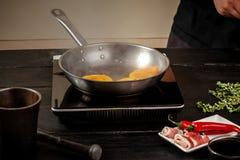 Pêssegos em uma bandeja de fritada Pêssegos do amarelo do fruto enlatado, fundo de madeira preto, placa Fotos de Stock