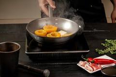 Pêssegos em uma bandeja de fritada Pêssegos do amarelo do fruto enlatado, fundo de madeira preto, placa Imagens de Stock