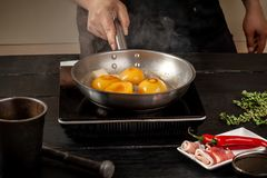 Pêssegos em uma bandeja de fritada Pêssegos do amarelo do fruto enlatado, fundo de madeira preto, placa Imagens de Stock Royalty Free