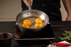 Pêssegos em uma bandeja de fritada Pêssegos do amarelo do fruto enlatado, fundo de madeira preto, placa Foto de Stock Royalty Free